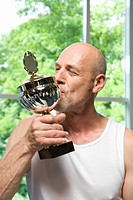 A man kissing a trophy