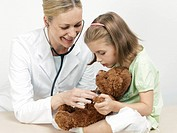 Female pediatrician examining a girl´s teddy bear