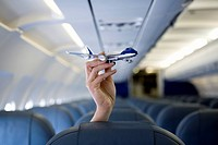 A hand holding a toy airplane above an airplane seat