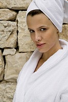 A woman wearing a bathrobe and her hair in a towel looking flirtatious