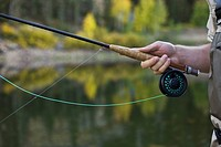 Detail of a man holding a fly rod