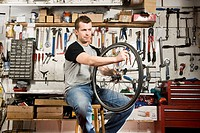 A man repairing a bicycle tyre in a workshop