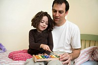A young girl sitting with her father and playing the xylophone