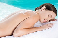 Young woman lying on towel by the pool with lotion on shoulder