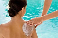 Young woman sitting by pool having lotion massaged into shoulders