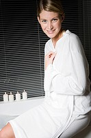 Portrait of young woman in bathrobe sitting on bathtub (thumbnail)