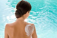Rear view of woman sitting by pool with lotion on shoulder