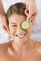 Smiling young woman lying on massage table with cucumber slice being placed over eye