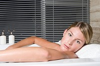 Young woman lying in bathtub
