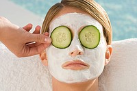 Woman with facial mask and cucumber slices over eyes