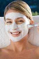 Smiling young woman brushing facial mask onto face