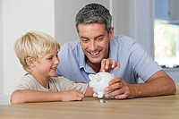Little boy putting coins in piggybank with his father