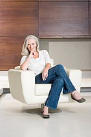 Portrait of middle aged woman sitting on modern armchair (thumbnail)