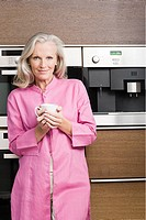 Middle aged woman standing in front of coffee machine with fresh cup of coffee