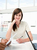 Smiling young businesswoman sitting at meeting table