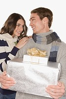 Happy couple holding gifts