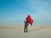 Businessman holding a red flag in a desert