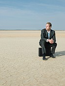 Businessman sitting in a desert