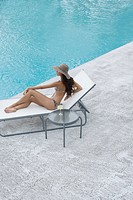 Glamorous woman on sunlounger by pool