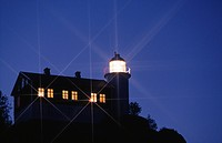Illuminated lighthouse under sky