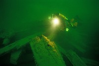 Diver swimming next to ship wreck the Baltic sea.