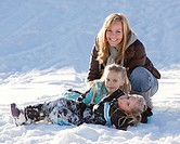 Mother and daughters playing in the snow