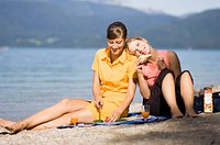 Two young women, girls, having a picnic on the lake shore, Lake Walchensee, Upper Bavaria, Bavaria, Germany