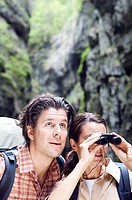 Couple hiking in the Partnachklamm, Woman looking through binoculars, Garmisch_Partenkirchen, Bavaria, Germany