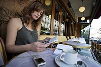 Young woman reading a book in a cafe, Paris, Ile de France, France