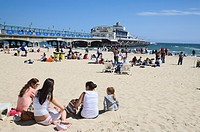 People relaxing at beach, pier with Pier Theatre in background, Bournemouth, Dorset, England, United Kingdom