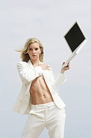 Young sexy businesswoman holding laptop on beach