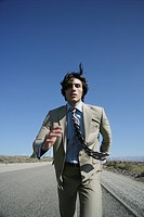 Young businessman in suit running down desolate highway.
