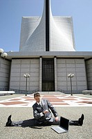 Portrait of young businessman doing split in front of building with laptop