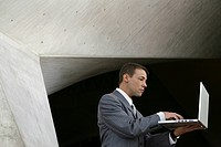 Businessman standing while typing on laptop indoors