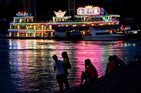 A group of people enjoy the lights of the swimming restraurant at the river bank in the evening, Chongqing, China, Asia