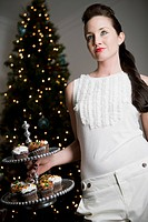 Portrait of young woman holding tray of cupcakes at Christmas