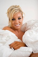 Portrait of sexy mature woman relaxing in bed