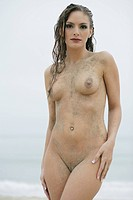 Naked young woman splattered with sand, portrait