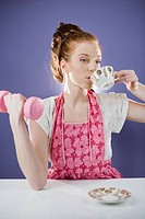 Young woman holding a dumbbell and having tea