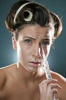 Young woman inserting syringe in her skin, portrait, close_up