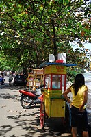 A woman standing next to a food stall at the roadside, Candi Dasa, East Bali, Indonesia, Asia