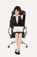 Businesswoman sitting on chair and using laptop, Business People