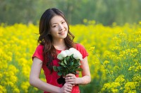 Young woman holding a bunch of flowers and standing in the flower field