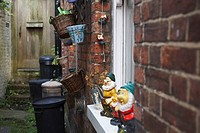 Alleyway with garden gnomes and refuse bins