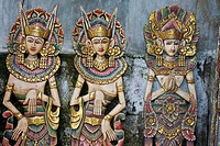 Three wooden figures of Balinese dancers in traditional dress in Ubud, Bali.