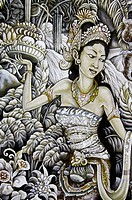 A painting of a Balinese woman in traditional dress carrying a bowl of fruit for a temple offering, walking in a garden.