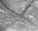 A cross_shaped crack in a stone.