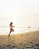 A woman jogging on a beach.