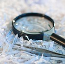 Confidential paperwork shredded with a magnifying glass and tweezers