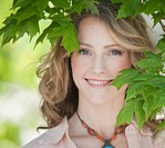 A woman outdoors surrounded in greenery